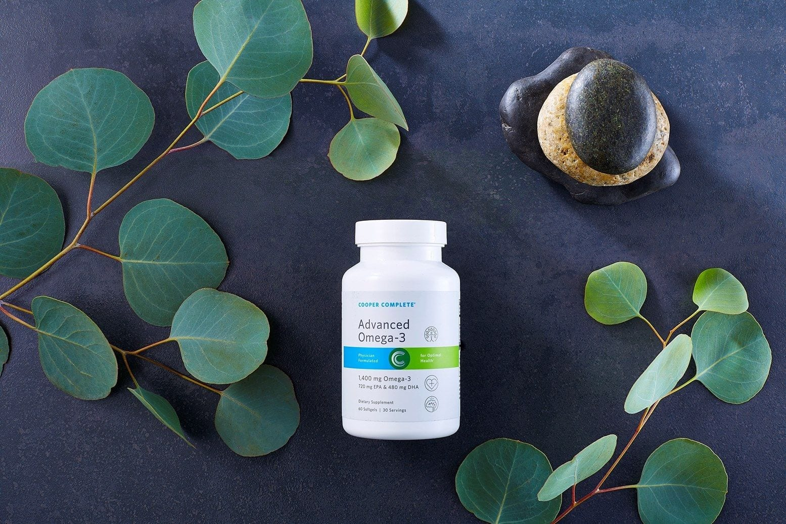 Cooper Complete Advanced Omega3 dietary supplement Bottle on a dark slate surface with green branches and several small stacked rocks