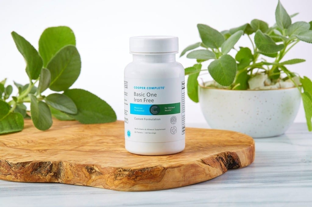 Cooper Complete Basic One Iron Free multivitamin and mineral bottle on a wood plank with cut and potted sage