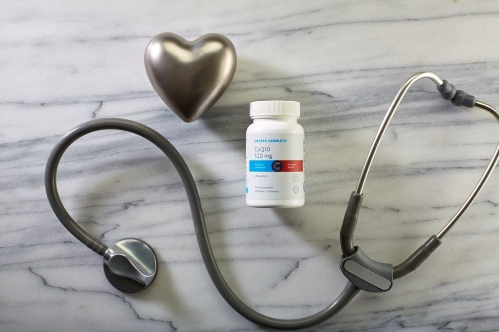 Cooper Complete CoQ10 50mg Ubiquinol dietary supplement bottle on a marble surface with stethoscope and metal heart shaped object