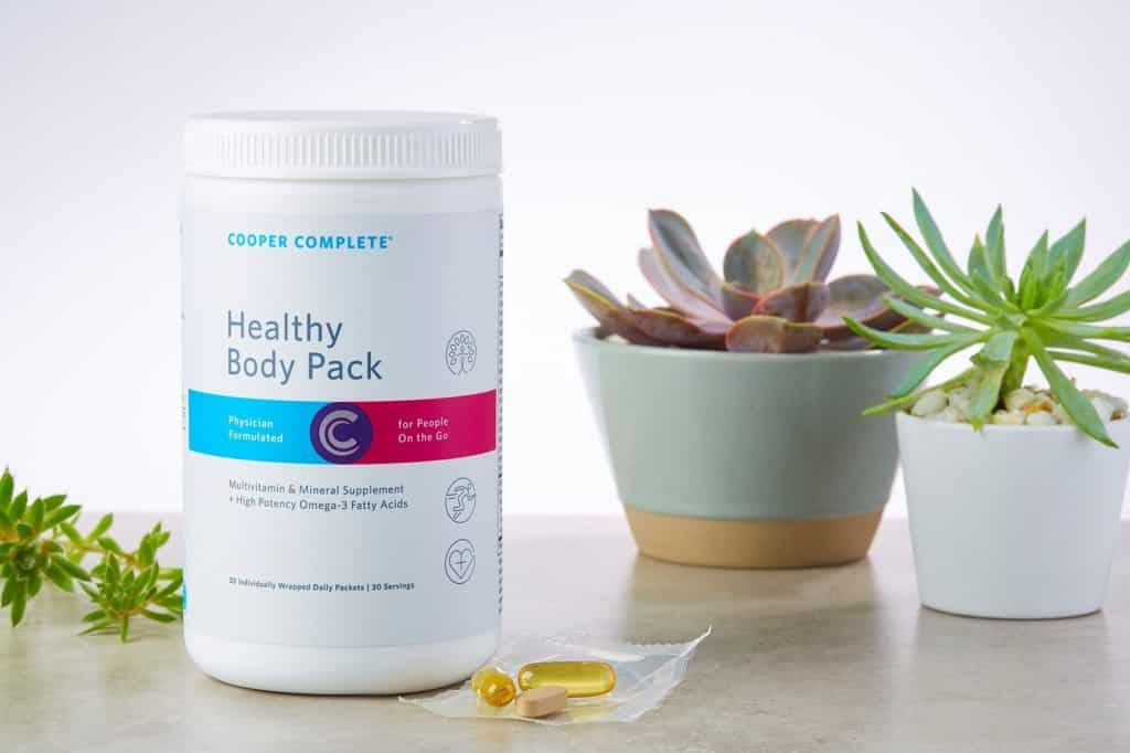 Cooper Complete Healthy Body Pack dietary supplement canister and a single daily packet on a counter with several succulent plants