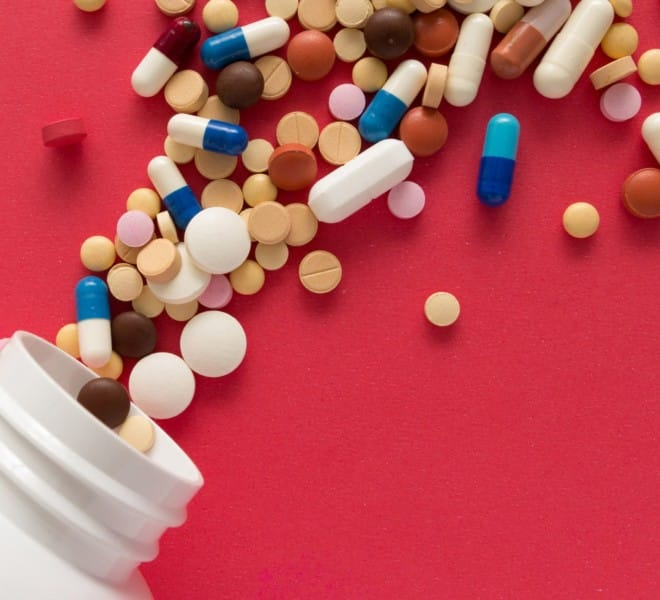 Bottle with pills and capsules of every color and size spilling out. The Cooper Complete team share common supplement misconceptions