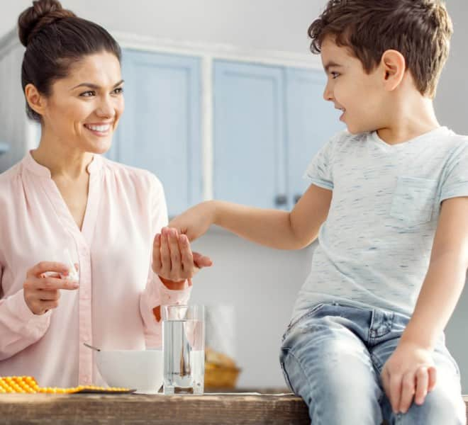 kids taking a supplement from their mom