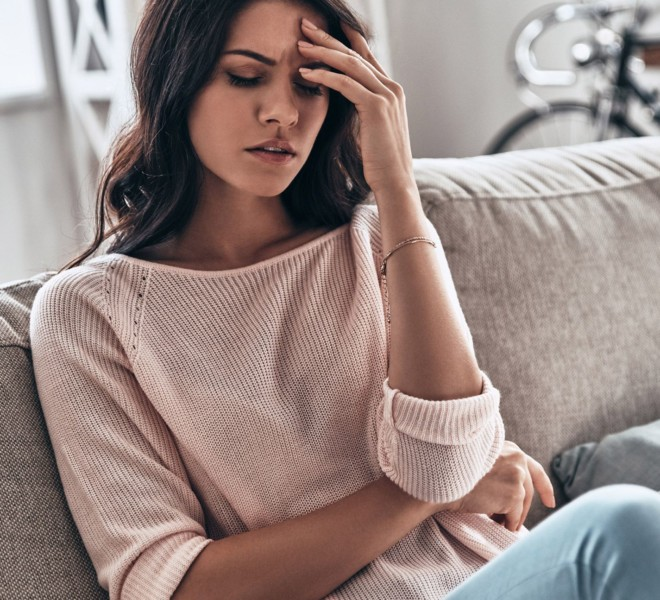 Migraine pains being felt by woman on a couch