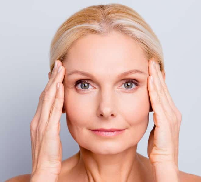 woman observing her dermatologic health in the mirror